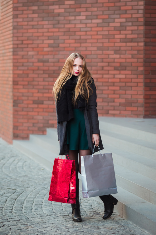 Young woman standing in front of red wall holding shopping bags Stock Photo 04