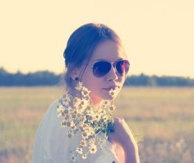 young woman wearing sunglasses and holding wildflowers in meadow Stock Photo
