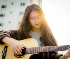 Asian girl sitting on the balcony playing guitar Stock Photo