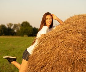 Beautiful girl and haystack Stock Photo
