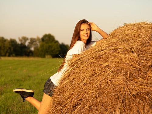 Beautiful girl and haystack Stock Photo