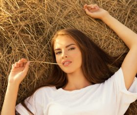 Beautiful girl with hay in her mouth Stock Photo