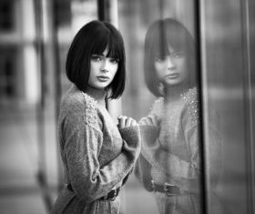 Black and white photo of woman standing in front of glass window Stock Photo