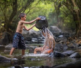 Children in the river holding bamboo baskets splashing water Stock Photo