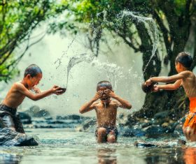 Children in the river splash each other Stock Photo