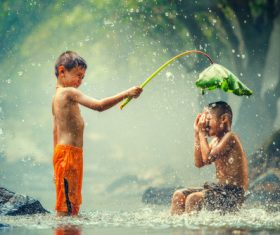 Children playing in the river with lotus leaves Stock Photo 02
