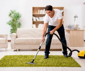 Cleaning the living room with vacuum cleaner Stock Photo