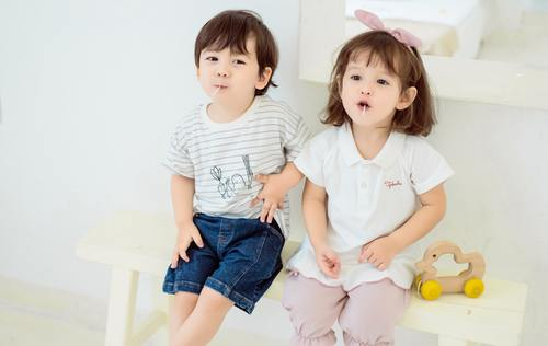 Cute little kids sitting together eating lollipops Stock Photo