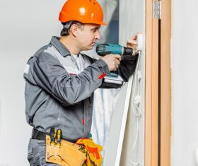 Electrician technician installing switch Stock Photo