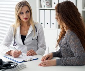 Female doctor asks the patient about the condition Stock Photo