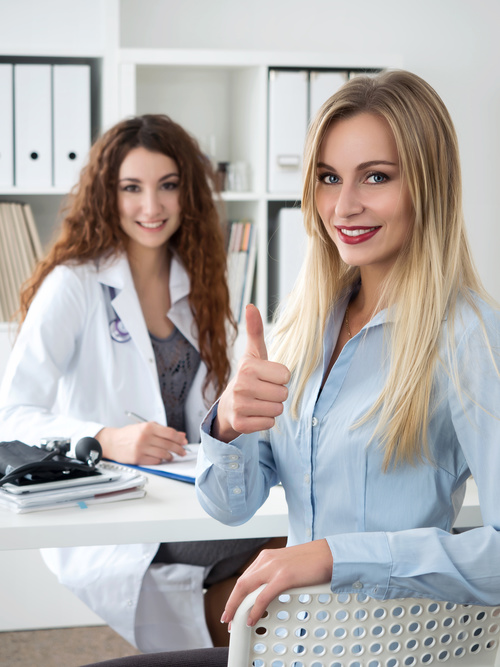 Female patient thumbs up praising female doctor Stock Photo
