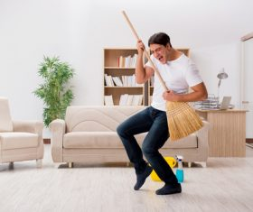 Funny man holding a broom Stock Photo