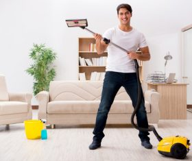 Funny man holding vacuum cleaner Stock Photo 02