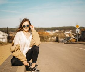 Hand support sunglasses woman sitting on the roadside Stock Photo