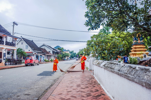Laos monks cleaning the road Stock Photo