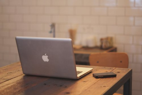 Laptop and mobile phone on wooden table Stock Photo