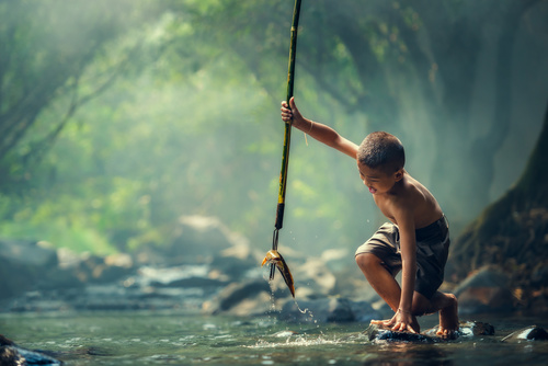 Little boy catching fish with harpoon in the river Stock Photo