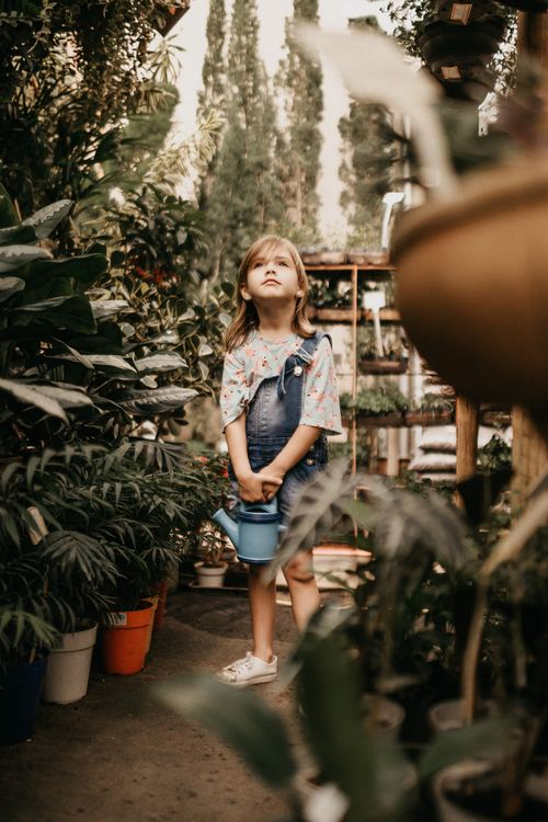 Little girl holding watering can in botanical garden Stock Photo