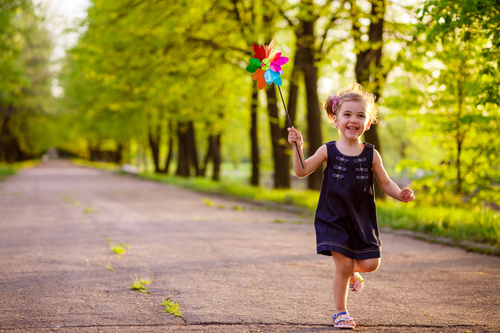 Little girl running with a windmill Stock Photo