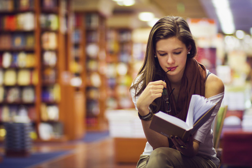 Long hair girl reading book in the library Stock Photo