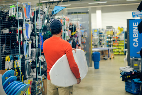 Man buys surfboard at the Sporting goods store Stock Photo