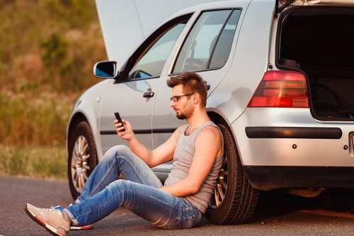 Man sitting next to the car and looking at the phone Stock Photo