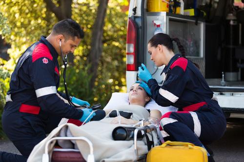 Paramedics rescuers check patient pupil Stock Photo