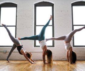 Three women doing handstand yoga moves Stock Photo