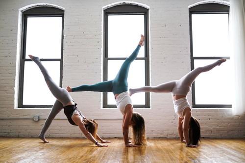 Three women doing handstand yoga moves Stock Photo