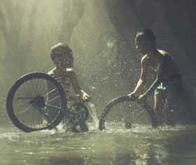 Two children cleaning bicycles in the river Stock Photo