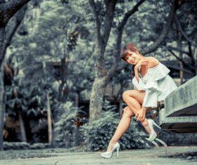 Wear high heels Asian women Sitting on the slate Stock Photo