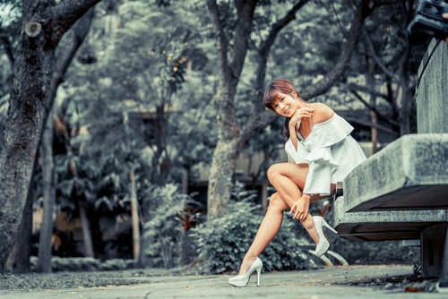 Wear high heels Asian women Sitting on the slate Stock Photo