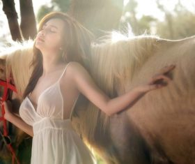 Wearing white dress closed eyes women and horse Stock Photo