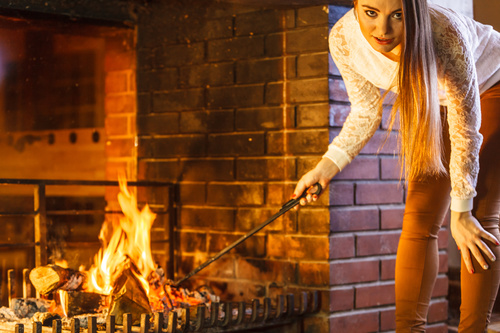 Woman adds wood to the fireplace Stock Photo