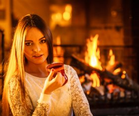 Woman drinking coffee by the fireplace Stock Photo 01