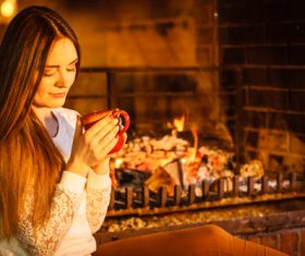 Woman drinking coffee by the fireplace Stock Photo 02