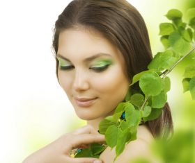 Woman green eyeshadow and green branches Stock Photo