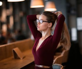Woman in glasses holds hair in hand Stock Photo