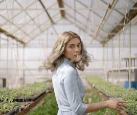 Woman in the greenhouse turned and looked Stock Photo