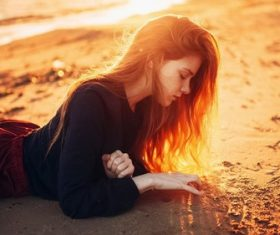 Woman kneeling on the beach writing on the beach Stock Photo