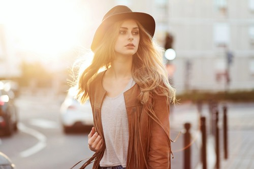 Woman on the street with black hat with blurred sunlight Stock Photo