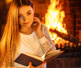 Woman reading a book by the fireplace Stock Photo