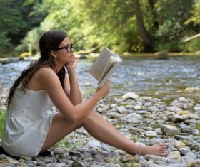 Woman reading book by the stream Stock Photo