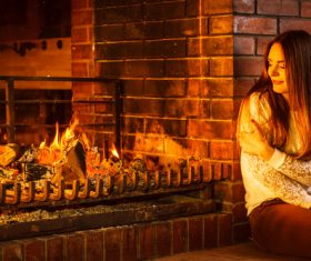 Woman relaxing at fireplace Stock Photo 01