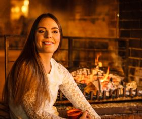 Woman relaxing at fireplace Stock Photo 02