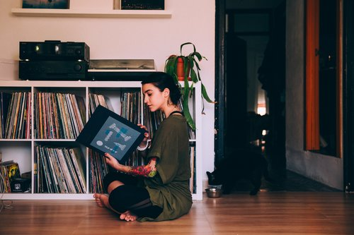 Woman sitting on the floor watching vinyl record Stock Photo