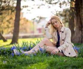 Woman sitting on the grass in the park with blue flowers Stock Photo