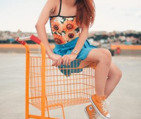 Woman sitting on the shopping cart Stock Photo