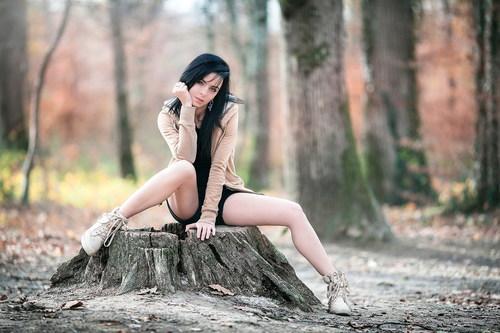 Woman sitting outdoors on tree stump Stock Photo