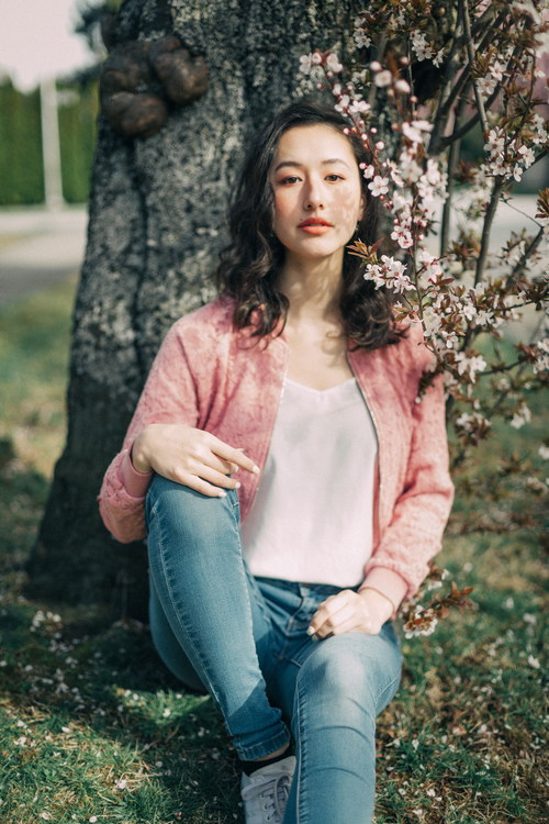 Woman sitting under the cherry tree Stock Photo
